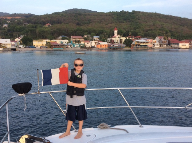 Ronan hoisting the courtesy flag, Deshaies, Guadeloupe