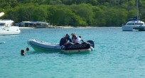 The kids getting pulled behind the dinghy, Salt Whistle Bay, Mayreau