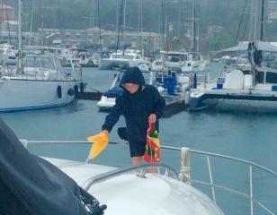 Ryan taking down the quarantine flag and hoisting the courtesy flag, Grenada