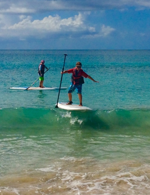 Ronan catching a wave on his stand up paddle board, Grand Anse Beach, Grenada